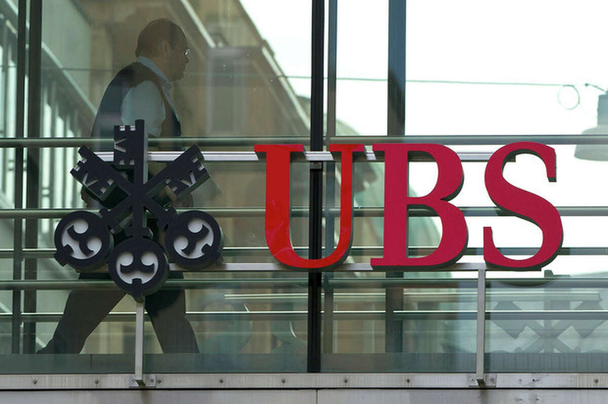 """FILE - In thos June 22, 2012 file photo a man walks past the logo of the UBS bank in Zurich, Switzerland. UBS AG posted second-quarter net profits of 425 million Swiss francs (US$434.16 million) Tuesday, July 31, 2012, a sharp plunge from the 1.02 billion Swiss francs (US$1.2 billion) it posted in the comparable period a year ago. Hit by lower trading revenue and fewer commissions and client fees, Switzerland's largest bank said the 58 percent net profit drop reflects """"challenging conditions marked by increased volatility and greater client caution."""" (AP Photo/Keystone, Alessandro Della Bella, File)"""