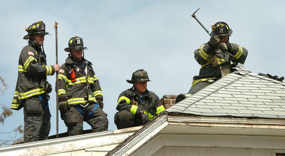 Hour Photo/Alex von Kleydorff Firefighter Jim Mills with Ladder Truck 2 vents the roof of a house on Lawrence St. that caught fire Tuesday afternoon.