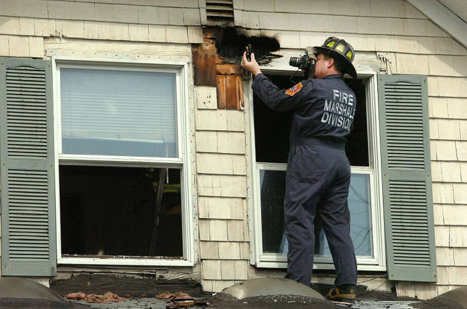 Hour Photo/Alex von Kleydorff Deputy Fire Marshal Chris Hansen takes a photo of an object of interest while checking the second floor exterior of a house on Lawrence St that caught fire Tuesday afternoon.