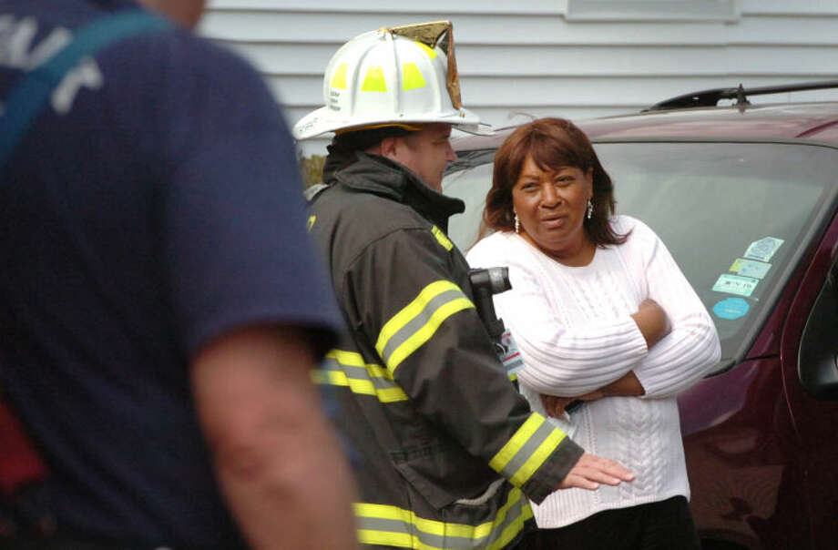 Hour Photo/Alex von Kleydorff Nellie Mann talks with Fire Personnel after her house on Lawrence St caught fire on Tuesday afternoon.