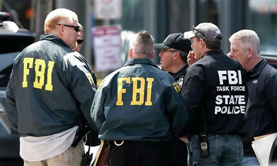 FBI agents gather near the finish line of the Boston Marathon in Boston Tuesday, April 16, 2013. The bombs that ripped through the crowd at the Boston Marathon, killing at least three people and wounding more than 170, were fashioned out of pressure cookers and packed with shards of metal, nails and ball bearings to inflict maximum carnage, a person briefed on the investigation said Tuesday. (AP Photo/Winslow Townson) / FR170221 AP