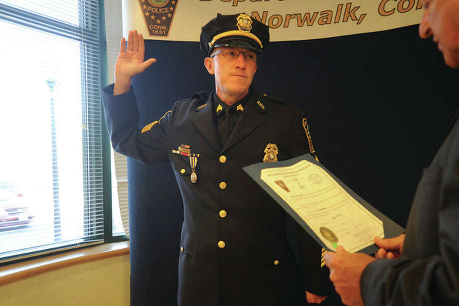 Hour photos / Matthew VinciAbove, left, Norwalk Police Sgt. Jim Walsh is promoted to lieutenant Monday at Norwalk Police Headquarters. Above right, fellow sergeant, Arthur Weisgerber, also became a lieutenant Monday. Officer Dean Russo, who was on vacation and could not attend the ceremony, will be promoted to sergeant when he returns.