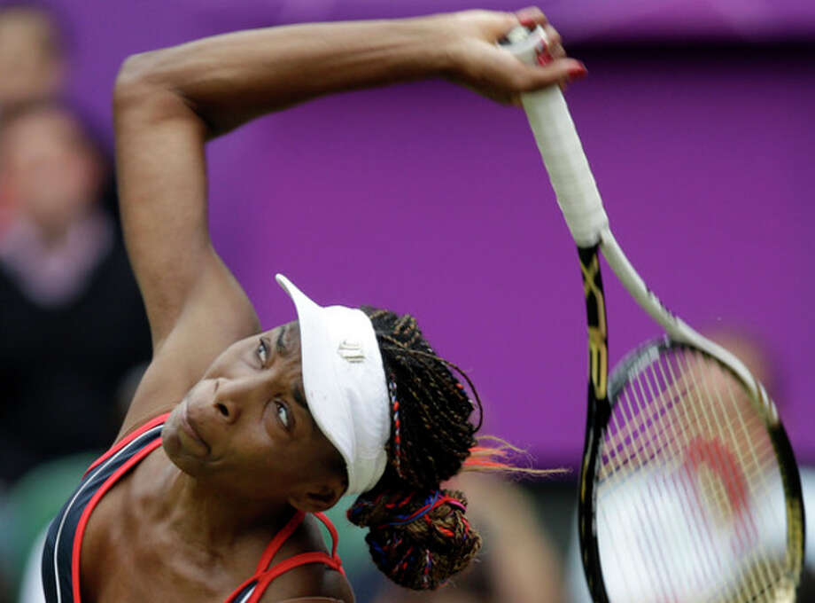 Venus Williams of the United States serves to Aleksandra Wozniak of Canada at the All England Lawn Tennis Club in Wimbledon, London at the 2012 Summer Olympics, Tuesday, July 31, 2012. (AP Photo/Elise Amendola) / AP