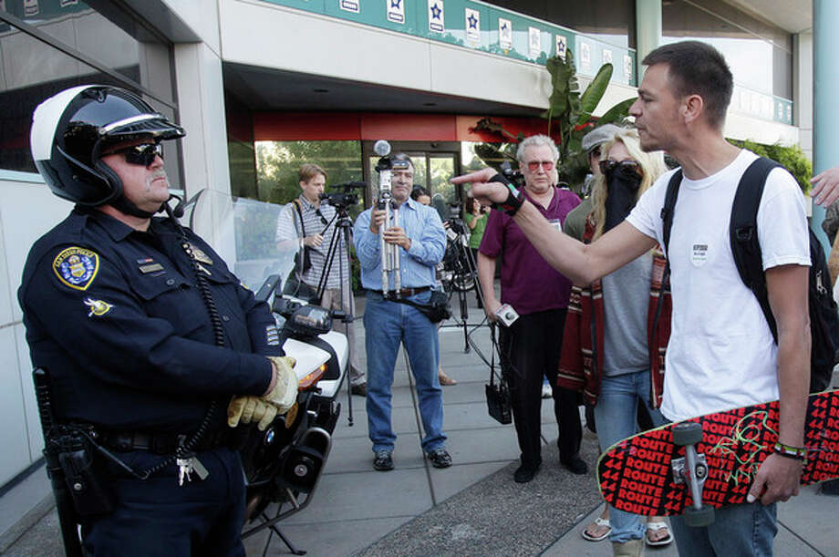 Josh Funn confronts San Diego Police officer B.A. Jackson outside police headquarters following the arrest of 51 Occupy San Diego protesters Friday, Oct. 28, 2011 in San Diego.   Dozens of police officers and San Diego County sheriff's deputies descended on the encampment around 2:30 a.m. Friday, declared an unlawful assembly and removed tents, canopies, tables and other furniture. (AP Photo/Lenny Ignelzi) / AP