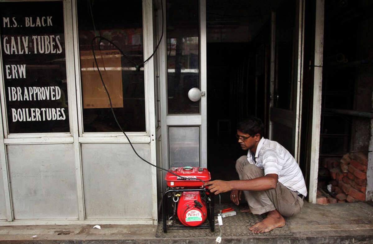 An Indian shopkeeper fixes an electric generator at his shop in New Delhi, India, Tuesday, July 31, 2012. India's energy crisis cascaded over half the country Tuesday when three of its regional grids collapsed, leaving 620 million people without government-supplied electricity in one of the world's biggest-ever blackouts. (AP Photo/Tsering Topgyal)