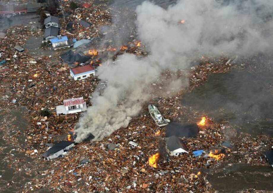 Flames rise from houses and debris half submerged in tsunami in Sendai, Miyagi Prefecture (state) after Japan was struck by a strong earthquake off its northeastern coast Friday, March 11, 2011. (AP Photo/Kyodo News) MANDATORY CREDIT, NO LICENSING ALLOWED IN CHINA, HONG KONG, JAPAN, SOUTH KOREA AND FRANCE
