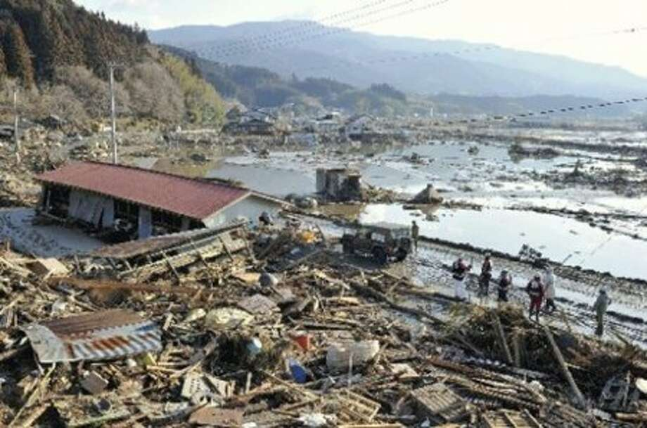 Rescue workers stand by totally shattered houses by a port in Rikuzentakada in Iwate Prefecture (state), northern Japan, Saturday morning, March 12, 2011, a day after a strong earthquake-triggered devastating tsunami hit the area. (AP Photo/Masamine Kawaguchi, The Yomiuri Shimbun) JAPAN OUT, CREDIT MANDATORY