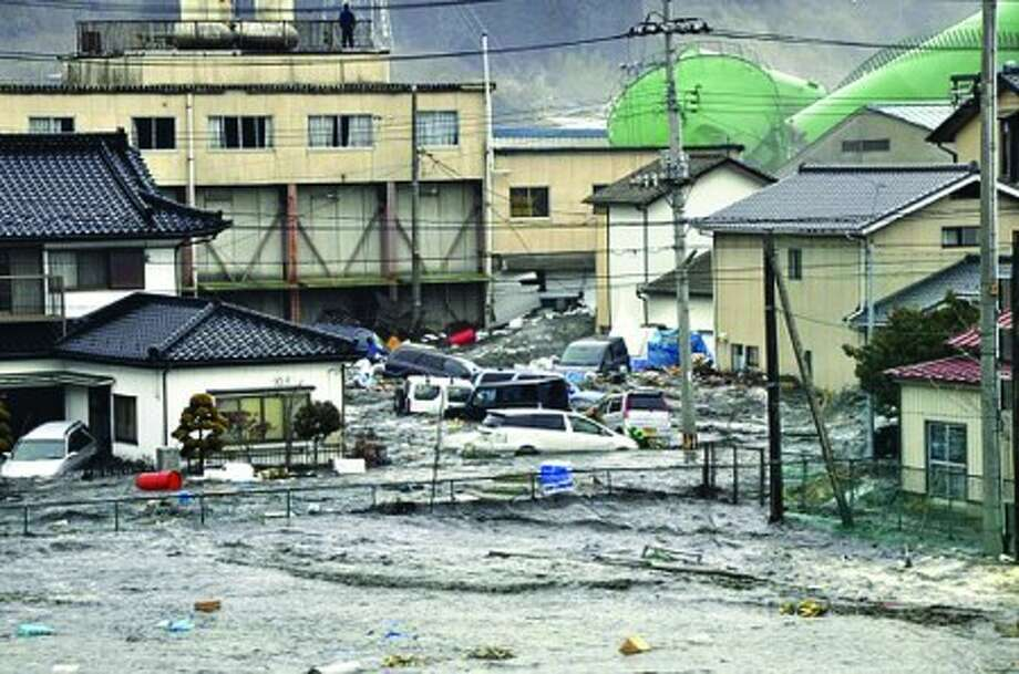 An earthquake-triggered tsunami washes away a warehouse and vehicles in Kesennuma, Miyagi prefecture (state), Japan, Friday March 11, 2011. The ferocious tsunami spawned by one of the largest earthquakes ever recorded slammed Japan''s eastern coasts. (AP Photo/The Yomiuri Shimbun) JAPAN OUT, CREDIT MANDATORY
