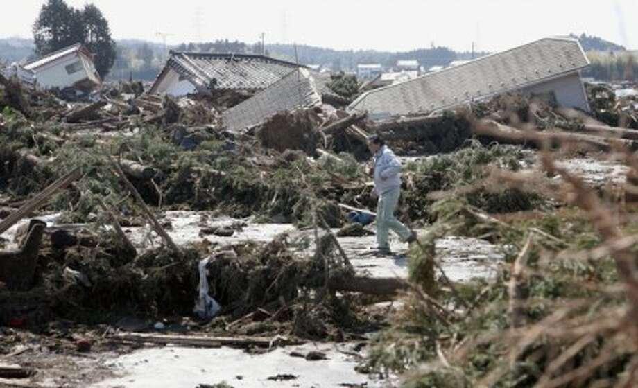 Man walks through houses devastated by tsunami in Minami Soma, Fukushima, northern Japan Saturday, March 12, 2011 after Japan''s biggest recorded earthquake slammed into its eastern coast Friday. (AP Photo/Kyodo News) MANDATORY CREDIT, NO LICENSING ALLOWED IN CHINA, HONG KONG, JAPAN, SOUTH KOREA AND FRANCE