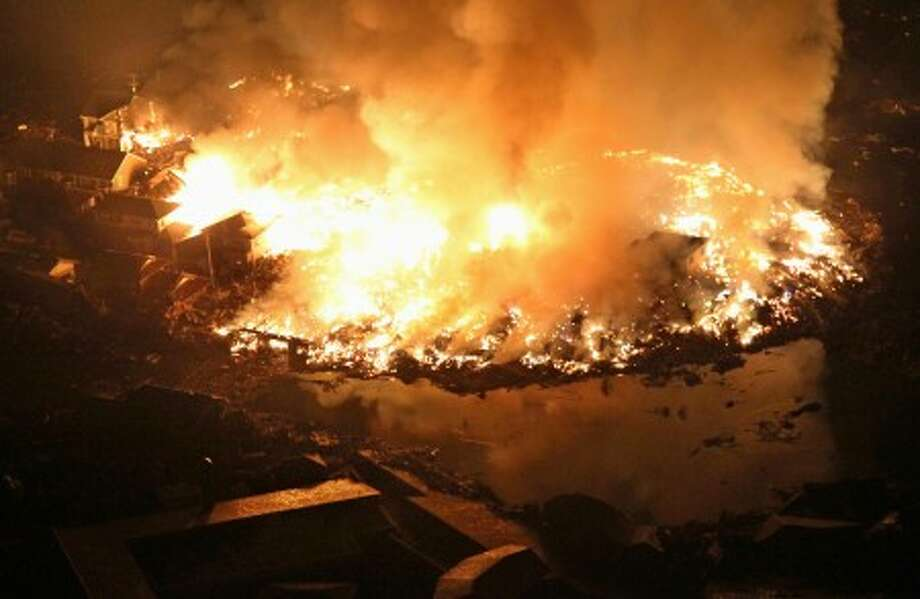 Houses and others burn in Natori, Miyagi Prefecture (state) Friday night, March 11, 2011 after Japan was struck by a strong earthquake off its northeastern coast earlier in the day. (AP Photo/Kyodo News) MANDATORY CREDIT, NO LICENSING ALLOWED IN CHINA, HONG KONG, JAPAN, SOUTH KOREA AND FRANCE