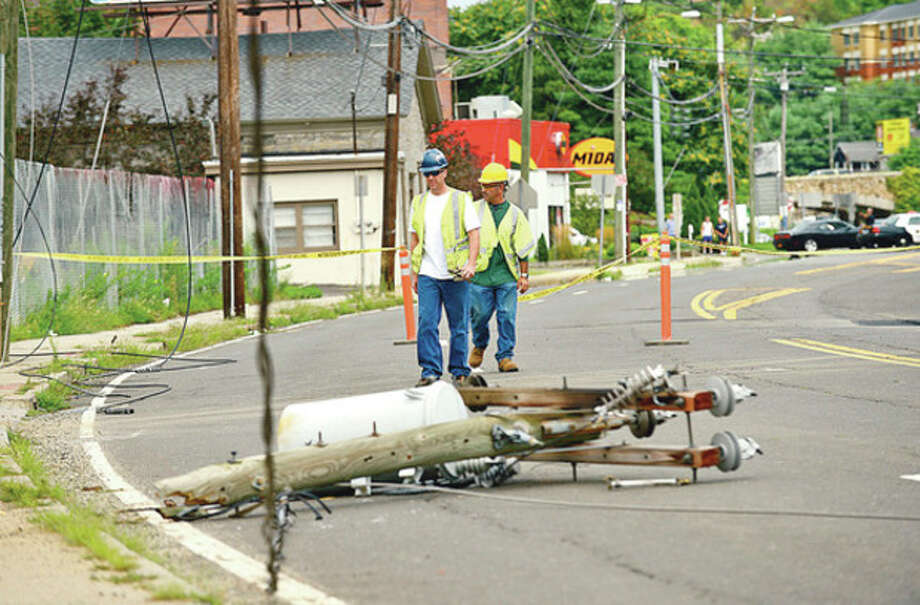 CL&P workers inspect a downed utilily pole on Main Ave that closed the road for several hours and leaving businesses without power until early evening.Hour photo / Erik Trautmann / (C)2012, The Hour Newspapers, all rights reserved