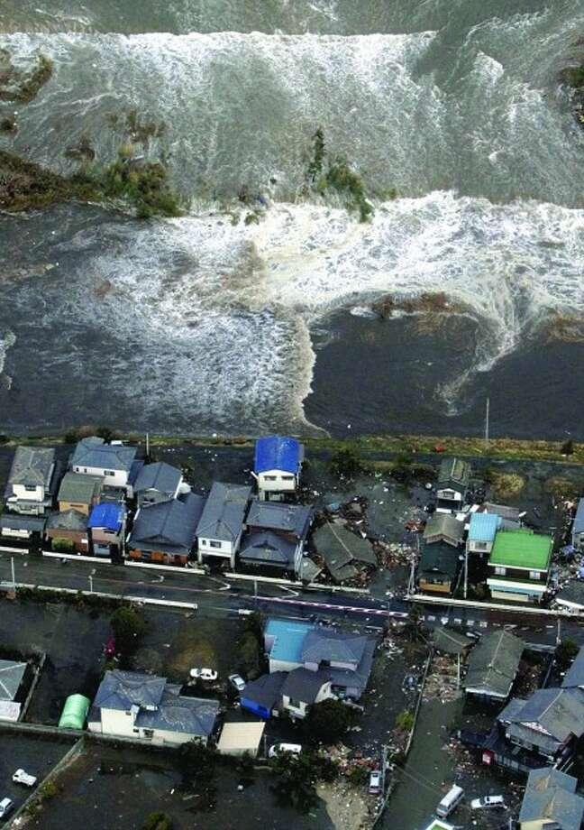 A tsunami approaches seashore houses in Kita Ibaraki, Ibaraki Prefecture, northeast of Tokyo, Friday, March 11, 2011 after the largest earthquake in Japan''s recorded history slammed the eastern coast. (AP Photo/The Yomiuri Shimbun, Yasushi Nagao) JAPAN OUT, CREDIT MANDATORY