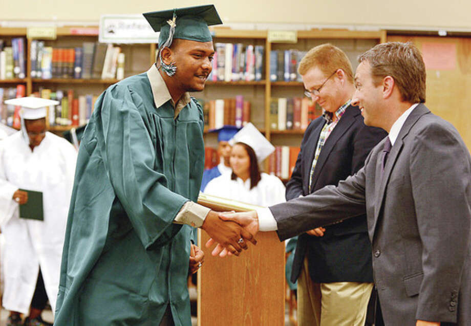 Hour photo / Erik TrautmannNorwalk High School graduate Matthew Raj recieves congratulations from state Sen. Bob Duff, D-25, during the graduation ceremony Tuesday morning at Norwalk High School for students from the summer school program. / (C)2012, The Hour Newspapers, all rights reserved