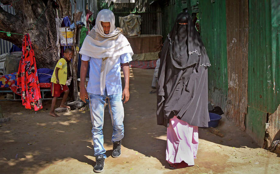 In this photo taken Wednesday, March 13, 2013, Abdi Ali, 25, and his girlfriend Anisa, 23, walk out after being married by an Islamic cleric who marries eloping couples, in Walaweyn, Somalia. Since the Islamic extremist rebels of al-Shabab have been pushed out of almost all of Somalia's cities and towns, life has begun to return to normal - including elopements which al-Shabab under its strict interpretation of Islamic Shariah law had declared illegal and punishable by whipping or even death by stoning. (AP Photo/Farah Abdi Warsameh) / AP