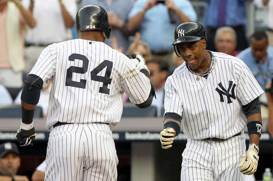 New York Yankees' Curtis Granderson, right, greets Robinson Cano after Cano hit a two-run home run during the first inning of a baseball game against the Baltimore Orioles, Tuesday, July 31, 2012, at Yankee Stadium in New York. (AP Photo/Seth Wenig) / AP