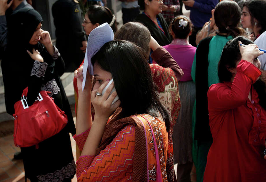 People evacuate buildings and call their relatives after a tremor of an earthquake was felt in Karachi, Pakistan, Tuesday, April 16, 2013. A major earthquake described as the strongest to hit Iran in more than half a century flatted homes and offices Tuesday near Iran's border with Pakistan, killing at least tens of people in the sparsely populated region and swaying buildings as far away as New Delhi and the skyscrapers in Dubai and Bahrain. (AP Photo/Shakil Adil) / AP