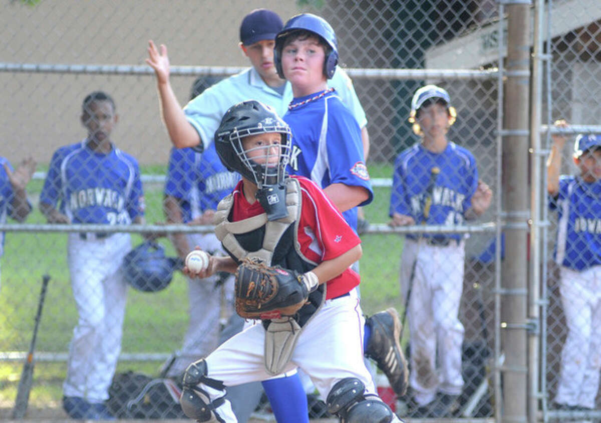 Hour photo/Matthew Vinci Norwalk Little League catcher Mike Dilorio watches the other runners after forcing Cal Ripken's Andrew Matthews at the plate during Monday's Kinlock Tournament game. Ripken outlasted Little League, 15-13, in a wild affair.