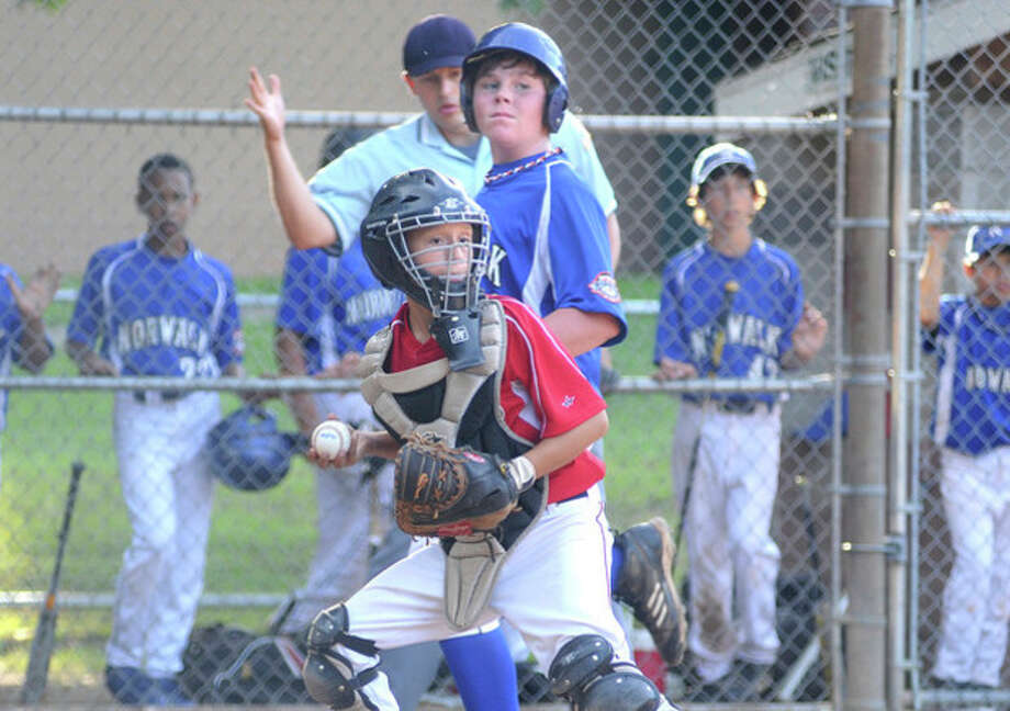Hour photo/Matthew VinciNorwalk Little League catcher Mike Dilorio watches the other runners after forcing Cal Ripken's Andrew Matthews at the plate during Monday's Kinlock Tournament game. Ripken outlasted Little League, 15-13, in a wild affair.