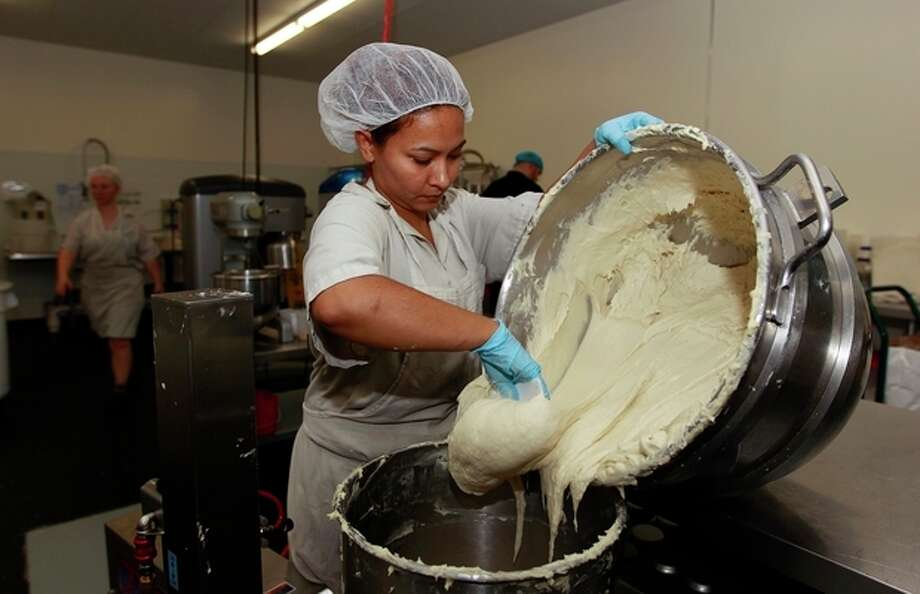 """In this Thursday, July 14, 2012 photo, Bertha Domimguez prepares gluten-free dough at Pure Knead bakery sandwich bread in Decatur, Ga. Scientists suggest that there may be more celiac disease today because people eat more processed wheat products than in decades past, which use types of wheat that have a higher gluten content. Or it could be due to changes made to wheat, said the Mayo Clinic's Dr. Joseph Murray. In the 1950s, scientists began cross-breeding wheat to make hardier, shorter and better-growing plants. It was the basis of a so-called """"Green Revolution"""" that boosted wheat harvests worldwide. (AP Photo/John Bazemore) / AP"""