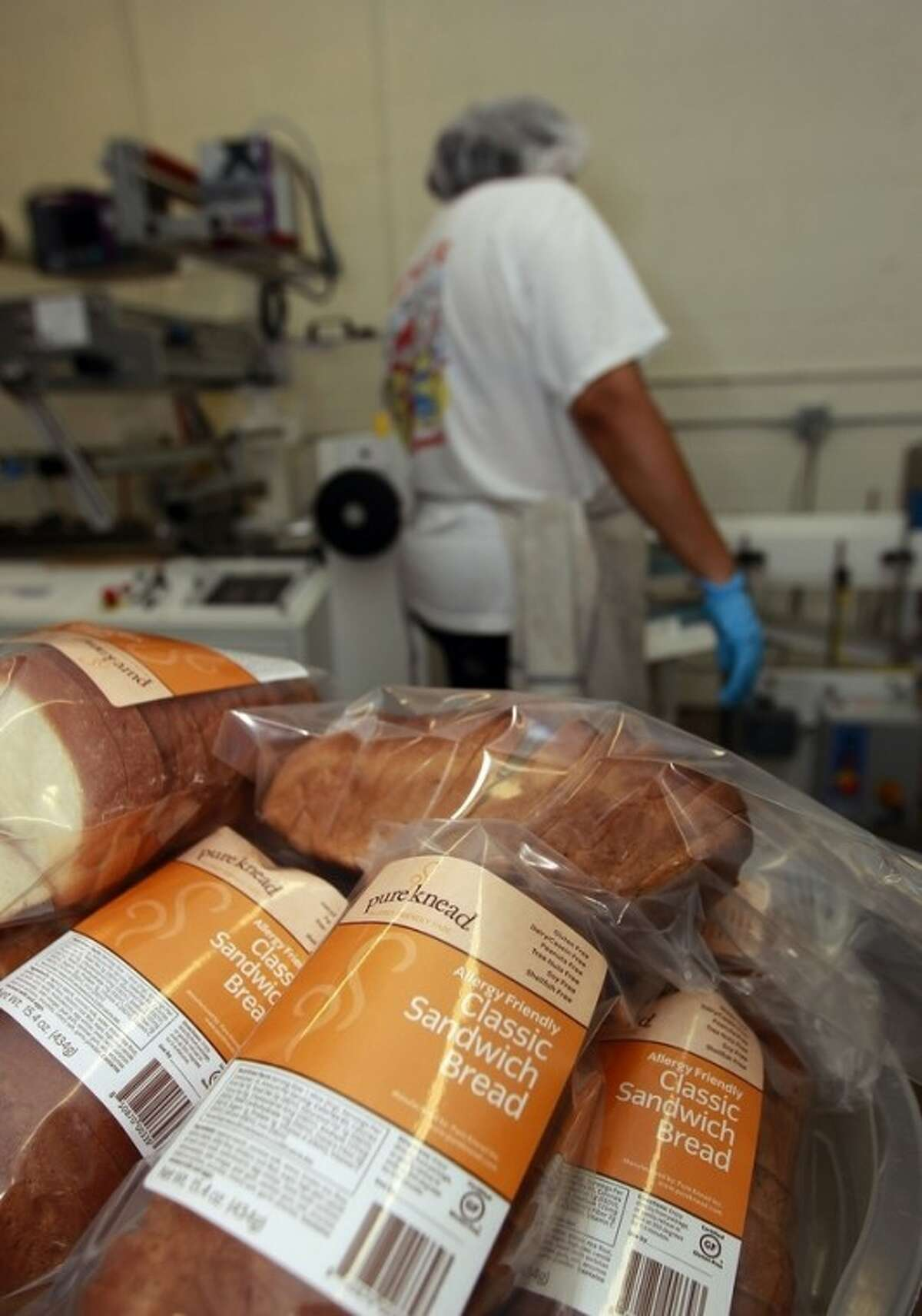In this Thursday, July 14, 2012 photo, a worker packages gluten-free bread at Pure Knead bakery sandwich bread in Decatur, Ga. A decade ago, virtually no one in the United States seemed to have a problem eating gluten in bread and other foods. Now, millions do and spend more than $7 billion on gluten-free products. Yet, experts estimate that more than half of those consumers don?'t have any clear-cut reaction to gluten. (AP Photo/John Bazemore)