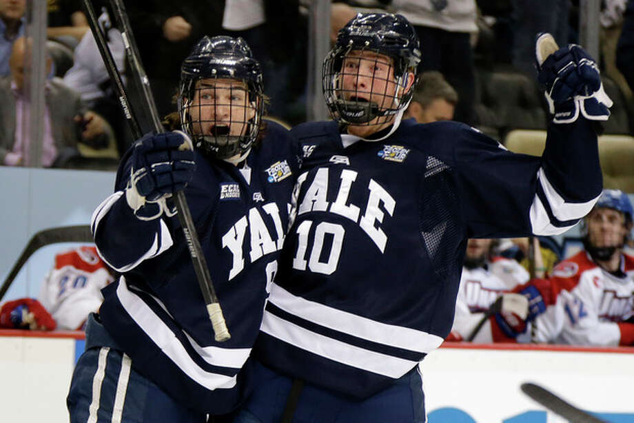 Yale forward Mitch Witek (10) celebrates his first-period goal with Carson Cooper (9) during an NCAA college hockey game against UMass Lowell in Pittsburgh, Thursday, April 11, 2013. (AP Photo/Gene Puskar) / AP