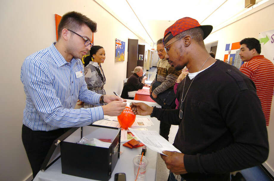 Hour Photo/Alex von Kleydorff Jeffrey Brown talks with banker Irving Amaral from the West Ave Branch, about teller positions with Wells Fargo Bank during the NEON Job Fair .