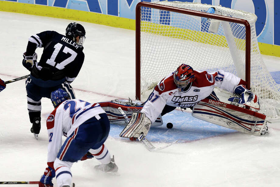 Yale right wing Andrew Miller (17) slips the puck between the legs of UMass Lowell goalie Connor Hellebuyck for the winning goal during overtime of an NCAA Frozen Four college hockey game in Pittsburgh, Thursday, April 11, 2013. Yale won 3-2. (AP Photo/Gene J. Puskar) / AP