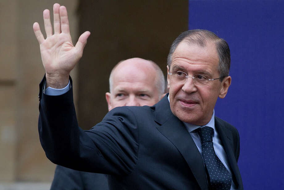 Russian Foreign Minister Sergey Lavrov, right, waves to the media as he walks with Britain's Foreign Secretary William Hague at the start of a G8 Foreign Ministers meeting in London, Thursday, April, 11, 2013. The ministers are meeting in London as Britain currently holds the G8 Presidency, with the heads of government G8 meeting set for June in Northern Ireland.(AP Photo/Alastair Grant) / AP