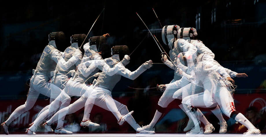 This multiple exposure photo shows France's Corinne Maitrejean and Italy's Elisa Di Francisca competing during a semifinals match at women's team foil fencing at the 2012 Summer Olympics, Thursday, Aug. 2, 2012, in London. (AP Photo/Pat Semansky) / AP