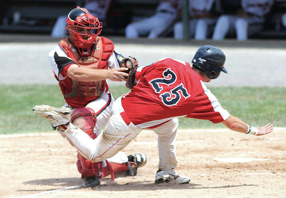 Hour Photo/John Nash Norwalk catcher Kevin Daniele ,left, stands fast as he tags out NianticÕs Al Lloyd on an attempted double steal in the second inning of SaturdayÕs American Legion state tournament game in Bristol. Norwalk advanced with an 8-2 victory.