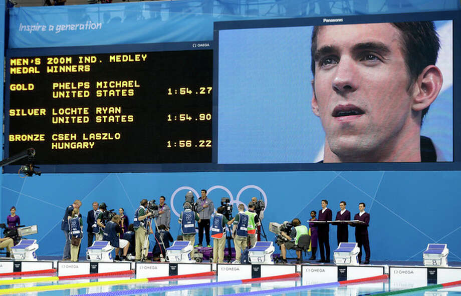 United States' Michael Phelps is seen on a giant display as he listens to the national anthem after receiving his gold medal for the men's 200-meter individual medley swimming final at the Aquatics Centre in the Olympic Park during the 2012 Summer Olympics in London, Thursday, Aug. 2, 2012. (AP Photo/Lee Jin-man) / AP