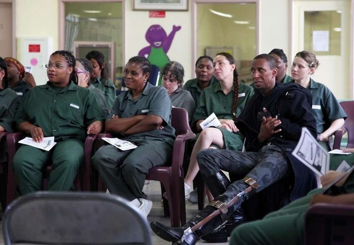 """This Monday, July 30, 2012 photo shows actor Ron Cephas Jones as Richard III siting among inmates during a performance of Shakespeare's """"Richard III"""" at the Taconic Correctional Facility in Bedford Hills, N.Y. Jones plays the physically deformed title monarch with a brace on his left leg. The medium-security prison was one stop that The Public Theater's Mobile Shakespeare Unit has made across the city over the past several weeks. (AP Photo/Mark Kennedy)"""