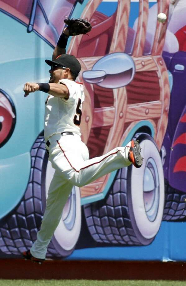 San Francisco Giants' Melky Cabrera jumps as he attempts to catch a double hit by New York Mets' Ronny Cedeno during the first inning of a baseball game, Thursday, Aug. 2, 2012, in San Francisco. (AP Photo/George Nikitin)