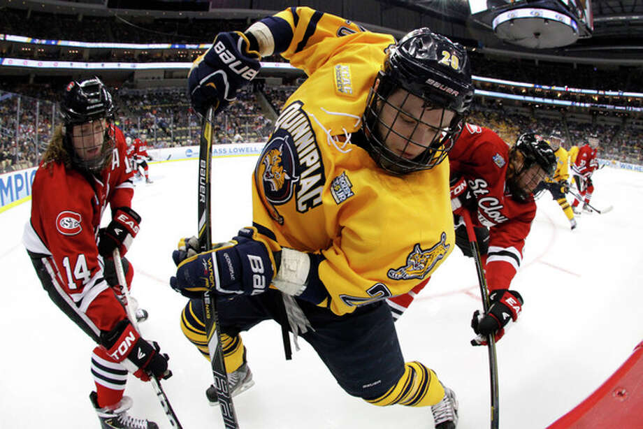 Quinnipiac forward Matthew Peca (20) works for the puck in the corner against St. Cloud State's Nick Jansen (14) and Cory Thorson during the first period of an NCAA college hockey Frozen Four semifinal tournament game in Pittsburgh, Thursday, April 11, 2013. (AP Photo/Gene J. Puskar) / AP