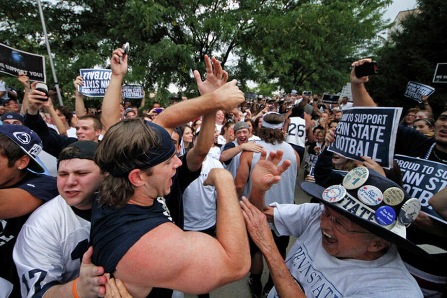 Penn State University linebacker Michael Mauti, second from left foreground, and his teammates are greeted by a pep rally of supporters on the way to a morning workout outside the Lasch Football building on the Penn State main campus in State College, Pa., Tuesday, July 31, 2012. (AP Photo/Gene J. Puskar) / AP