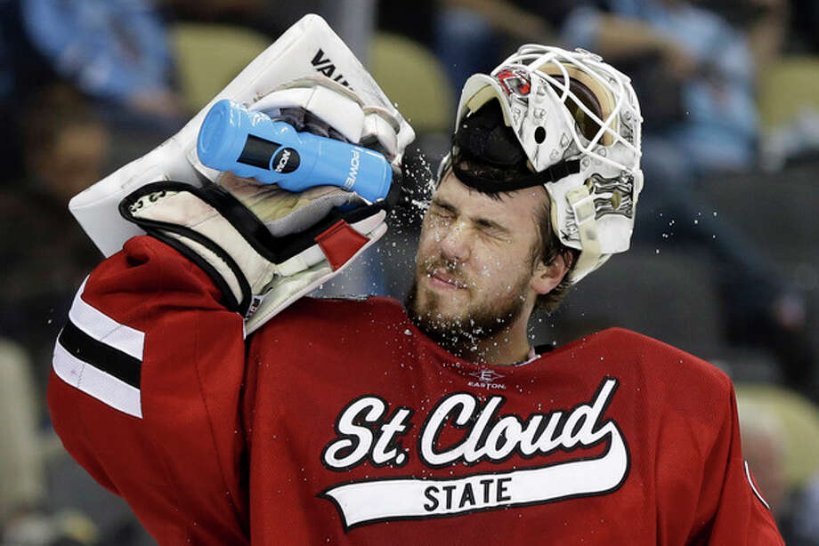 St. Cloud State goalie Ryan Faragher squirts water in his face after allowing a goal during the first period of an NCAA college hockey Frozen Four semifinal game against Quinnipiac in Pittsburgh, Thursday, April 11, 2013. (AP Photo/Gene J. Puskar) / AP