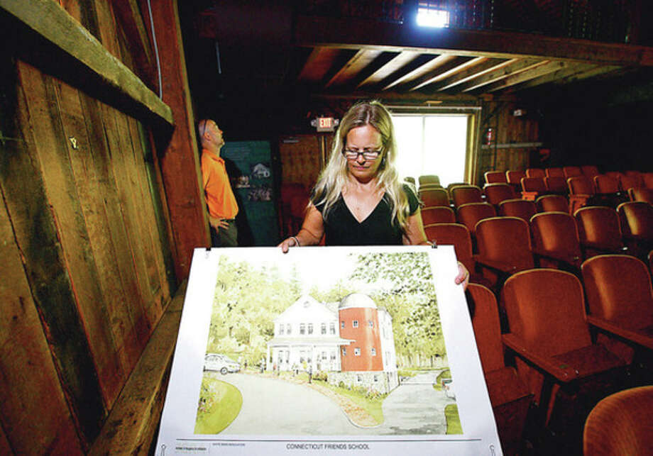 Kim Tsocanos, co-head of CT Friends School, looks over a rendering of a renovated White Barn theater at Connecticut Friends School at their White Barn Campus in Norwalk Wednesday.Hour / Erik Trautmann / ©2012 The Hour Newspapers