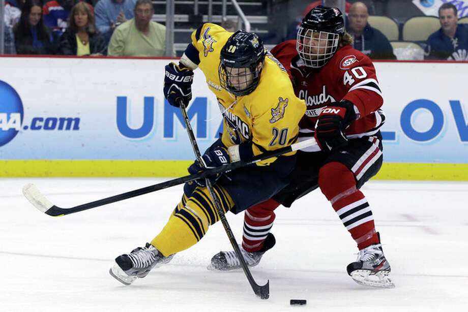 Quinnipiac forward Matthew Peca (20) can't get a shot off while being defended by St. Cloud State defenseman Tim Daley (40) during the first period of an NCAA college hockey Frozen Four semifinal tournament game in Pittsburgh, Thursday, April 11, 2013. (AP Photo/Gene J. Puskar) / AP