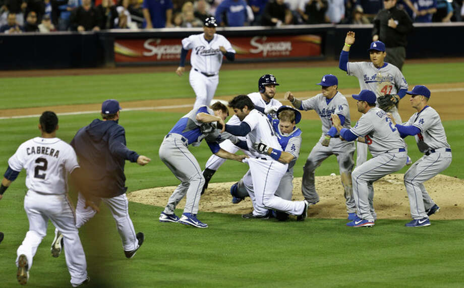 San Diego Padres' Carlos Quentin charges into Los Angeles Dodgers pitcher Zack Greinke after being hit by a pitch in the sixth inning of baseball game in San Diego, Thursday, April 11, 2013. (AP Photo/Lenny Ignelzi) / AP