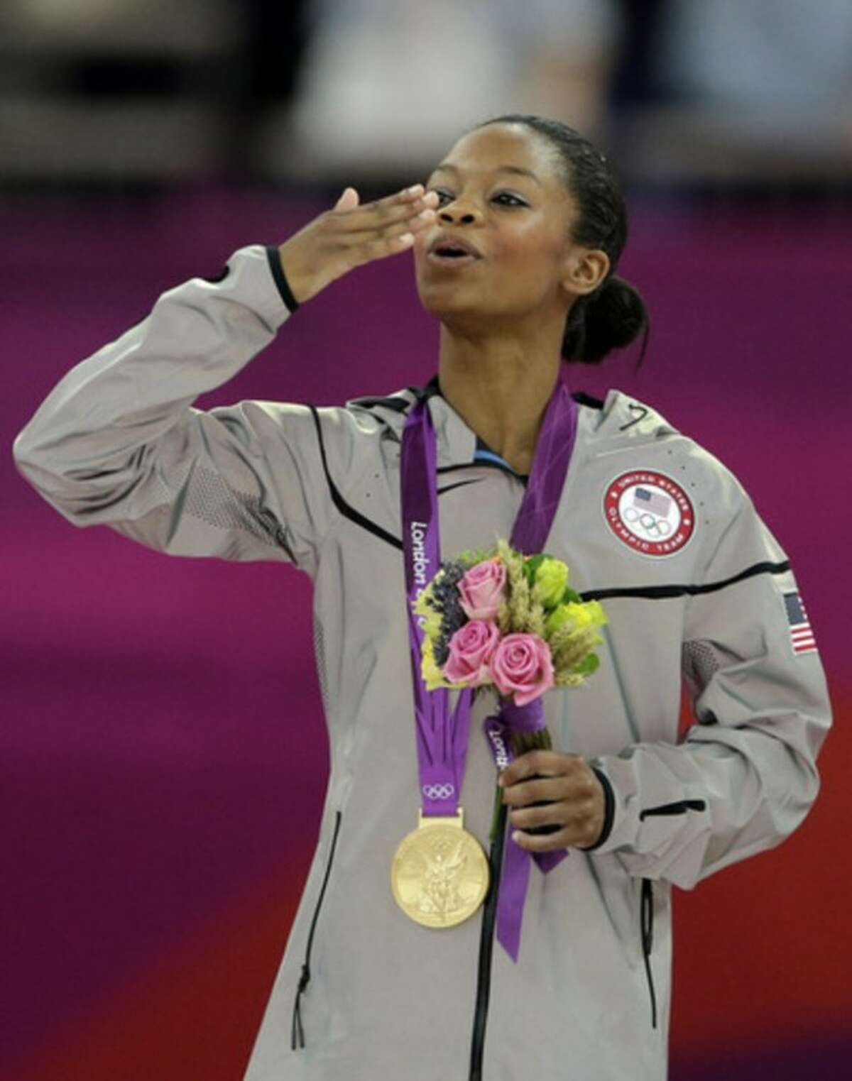 U.S. gymnast Gabrielle Douglas blows kisses to the crowd after receiving her gold medal during the artistic gymnastics women's individual all-around competition at the 2012 Summer Olympics, Thursday, Aug. 2, 2012, in London. (AP Photo/Gregory Bull)