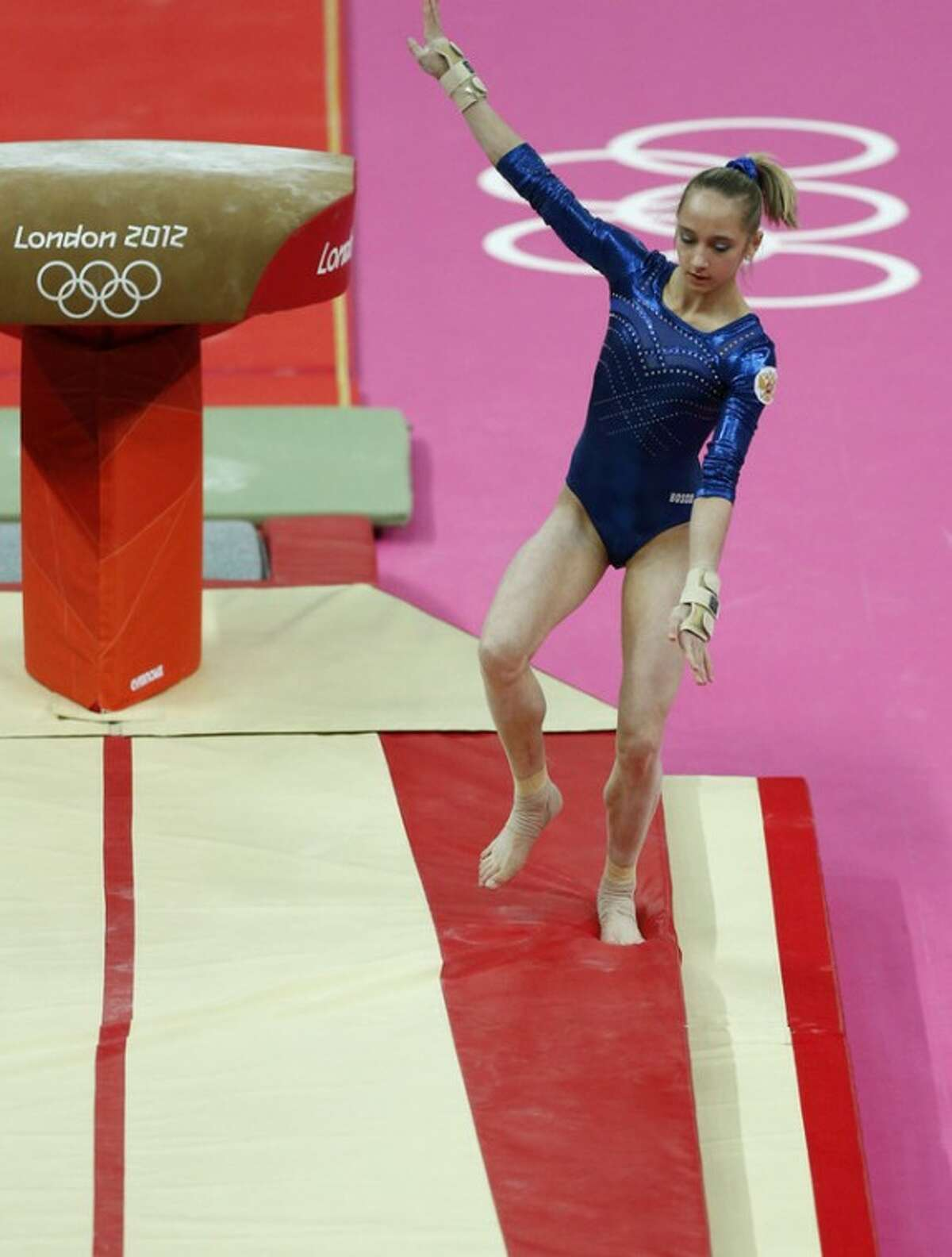 Russian gymnast Victoria Komova botches her dismount during the Artistic Gymnastics women's individual all-around competition at the 2012 Summer Olympics, Thursday, Aug. 2, 2012, in London. (AP Photo/Matt Dunham)