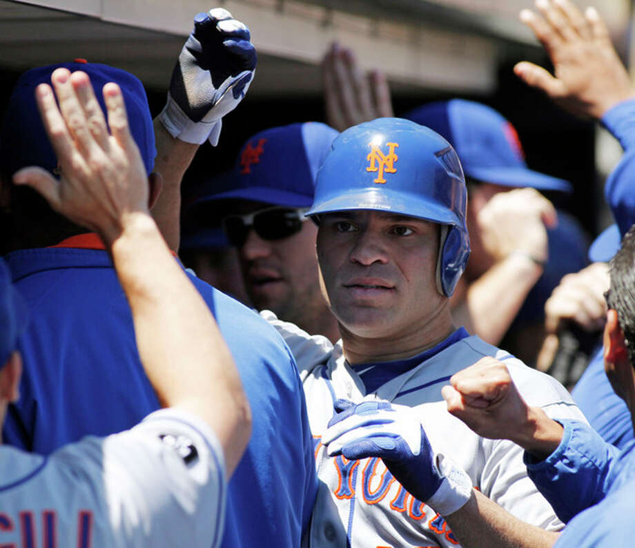New York Mets' Scott Hairston is greeted in the dugout after scoring on a Jason Bay single against the San Francisco Giants during the first inning of a baseball game, Thursday, Aug. 2, 2012, in San Francisco. (AP Photo/George Nikitin) / FR57659 AP