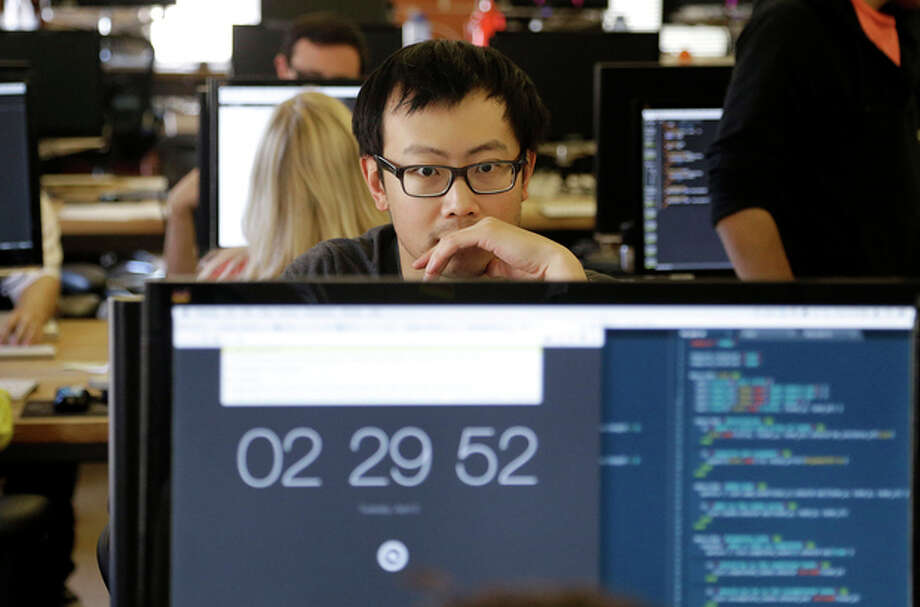 """Student David Wen works during a class at Dev Bootcamp in San Francisco, Tuesday, April 2, 2013. Dev Bootcamp is one of a new breed of computer-programming schools that's proliferating in San Francisco and other U.S. tech hubs. These """"hacker boot camps"""" promise to teach students how to write code in two or three months and help them get hired as web developers, with starting salaries between $80,000 and $100,000, often within days or weeks of graduation. (AP Photo/Jeff Chiu) / AP"""