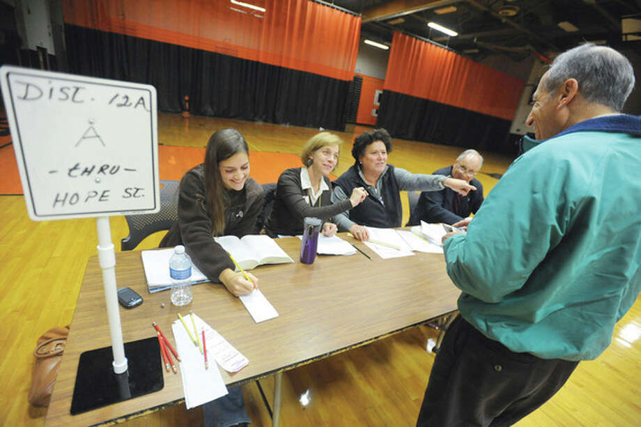 Photo by Matthew Vinci Election officials, from left, Olivia Welborn, Karen Welborn and Marcie Schoenfeld help voters at the Stamford High School polling center on Tuesday. / (C)2011, The Hour Newspapers, all rights reserved