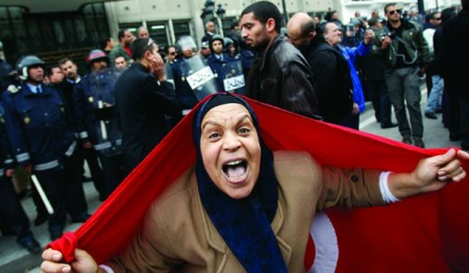 A protester with a Tunisian flag shouts slogans against President Zine El Abidine Ben Ali in Tunis, Friday, Jan. 14, 2011. Thousands of angry demonstrators marched through Tunisia''s capital Friday, demanding the resignation of the country''s autocratic leader a day after he appeared on TV to try to stop deadly riots that have swept the North African nation. (AP Photo/Christophe Ena)