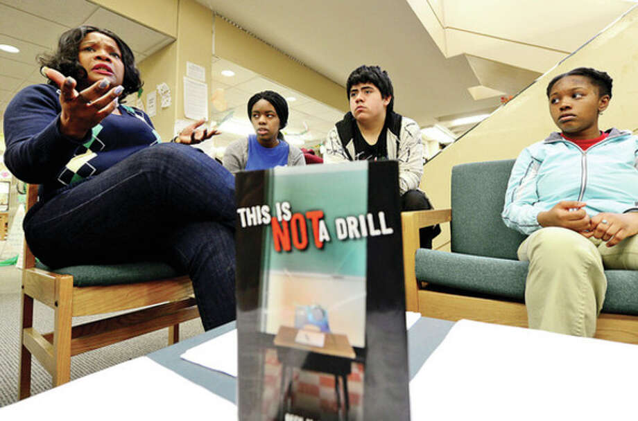 Library Media Specialist, Willette Payton, speaks to the Norwalk High School Lunch Bunch Book Club members including Jasmine Dautruche, Alfredo Lopez and Felia Moresca as they discuss the book This is Not a Drill and their feelings on the Sandy Hook and other school shootings.Hour photo / Erik Trautmann / (C)2013, The Hour Newspapers, all rights reserved
