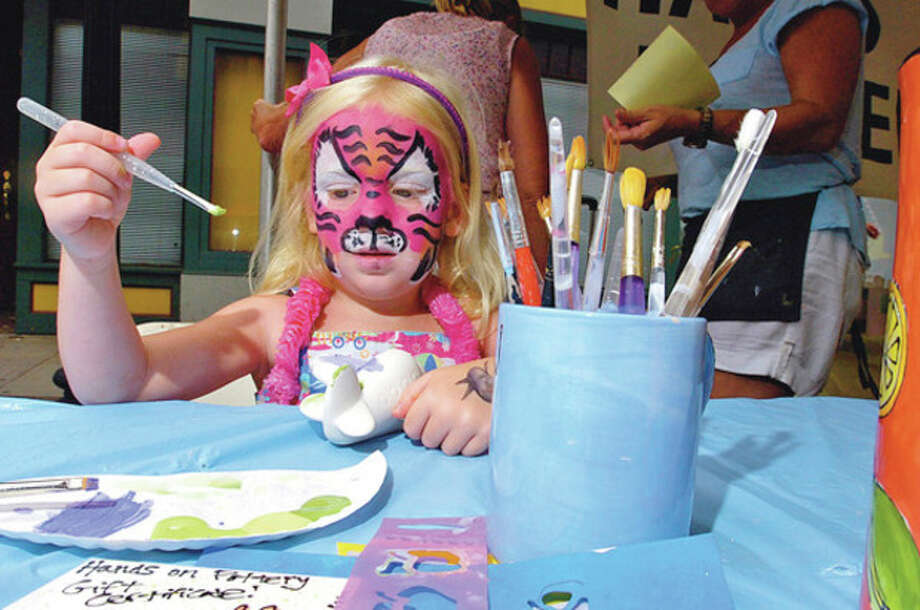 Ava Salbati paints a sculpture at Hands On Pottery booth Saturday at the 2011 SoNo Arts Festival.Hour photo / Erik Trautmann / (C)2011, The Hour Newspapers, all rights reserved