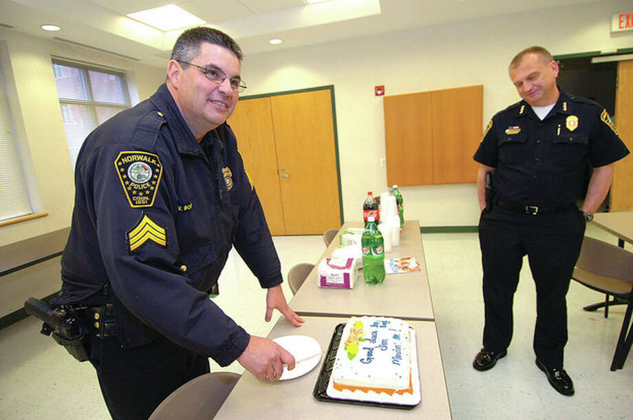 Hour Photo/Alex von Kleydorff Norwalk Police Chief Tom Kulhawik watches as Sgt Jim Boff cuts a good luck cake for 25 officers gathered to wish him well on his retirement from the police force. / 2013 The Hour Newspapers