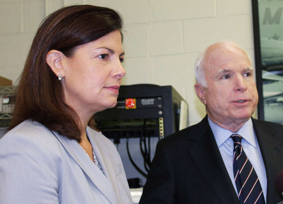 U.S. Sen. Kelly Ayotte, R-N.H., left, listens as Sen. John McCain, R-Ariz., speaks to the media after a town hall meeting Tuesday, July 31, 2012 in Merrimack, N.H. Tuesday's town hall meeting in Merrimack was the final stop on McCain's two-day tour designed to sound the alarm about the automatic, across-the-board cuts that are part of a $1.2 trillion deficit-cutting plan. (AP Photo/Holly Ramer) / AP