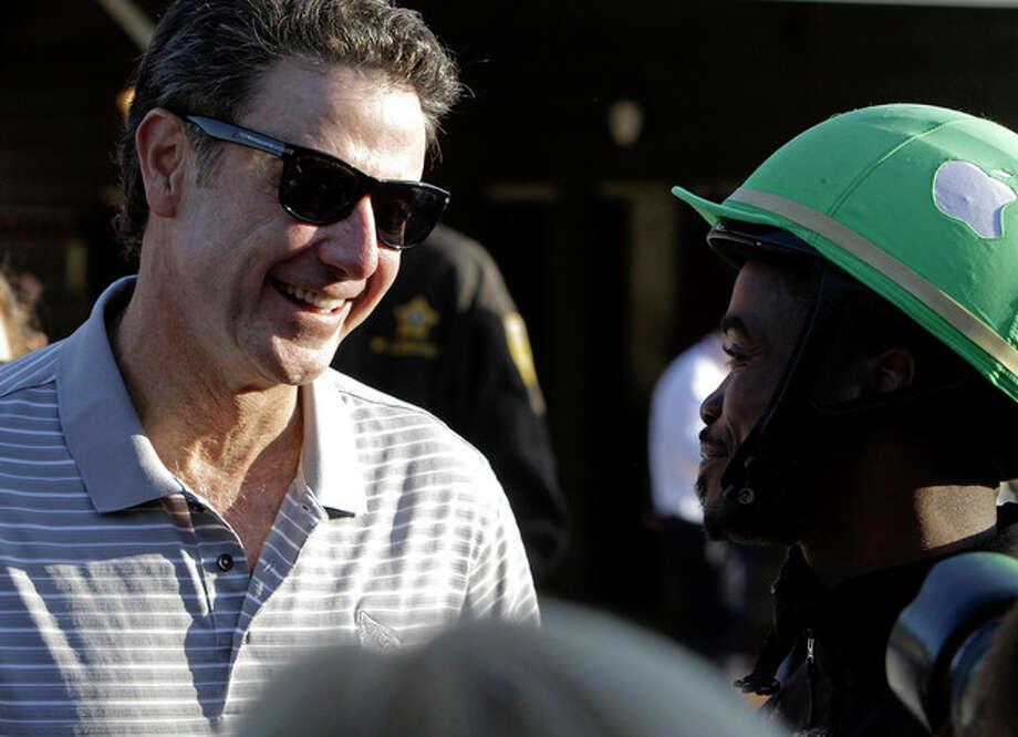 Part-owner of Kentucky Derby hopeful Goldencents Rick Pitino, left, talks to jockey Kevin Krigger at Churchill Downs Wednesday, May 1, 2013, in Louisville, Ky. (AP Photo/Garry Jones) / FR50389 AP